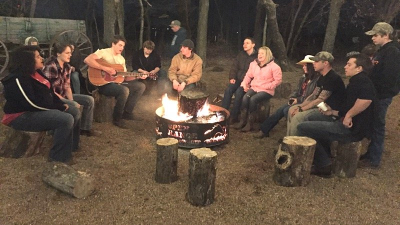 Youth group sharing stories, time, and music around the fire ring at church.